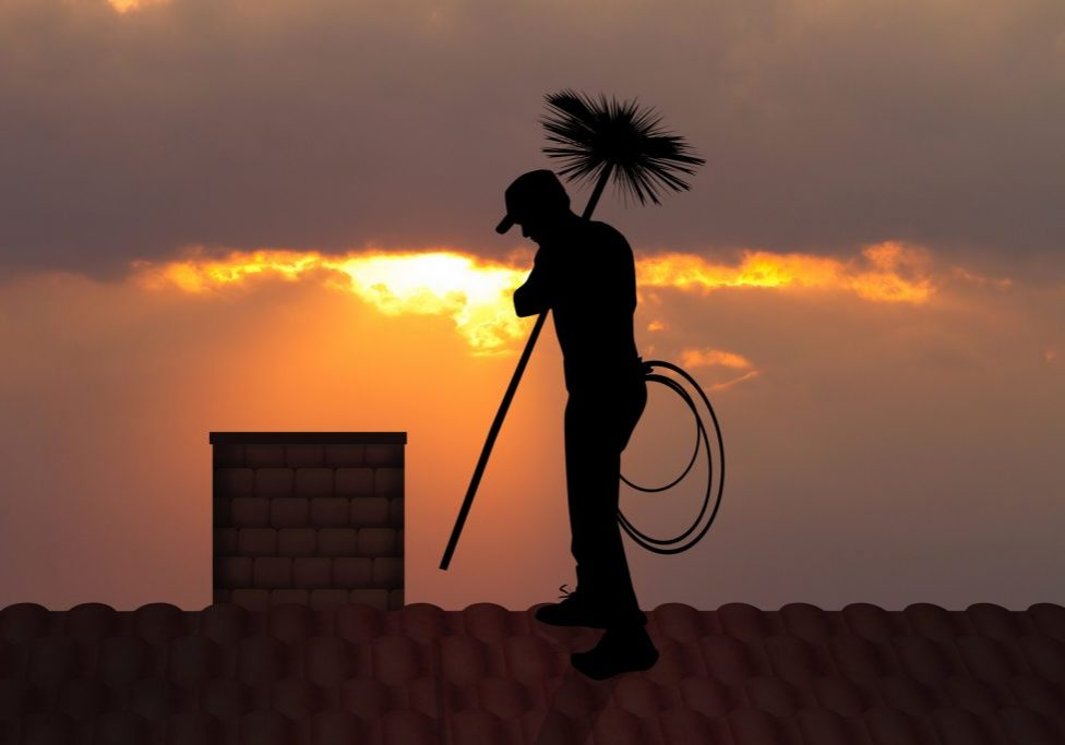 a silhouette of a man cleaning the chimney